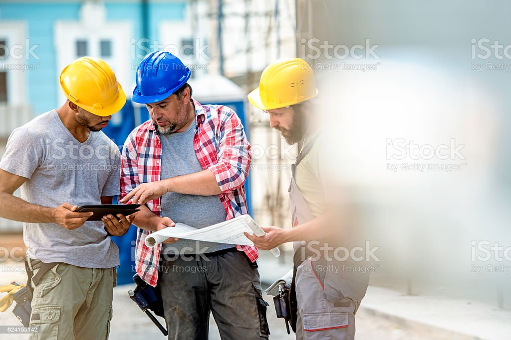 Three construction workers preparing for work stock photo