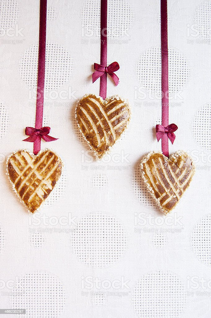 Three cookies in shape of heart with little bows royalty-free stock photo
