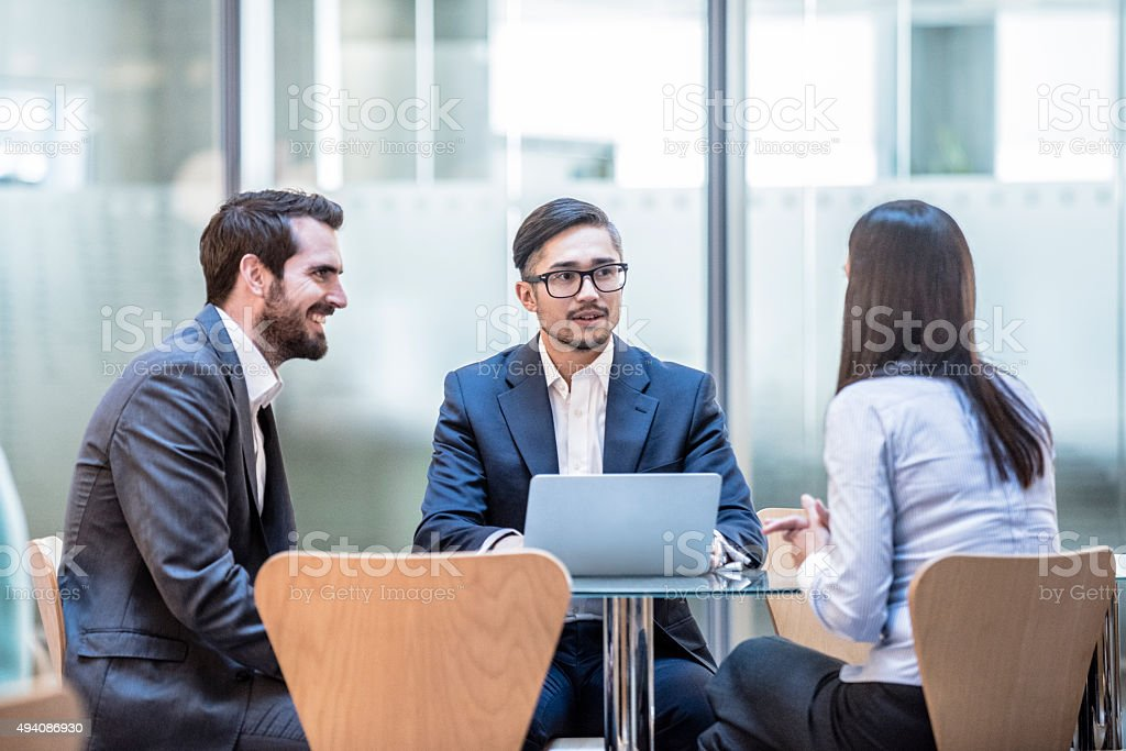 Three corporate business people in meeting with laptop. stock photo