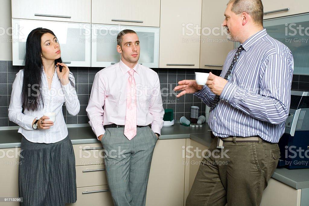 Three coworker in the break room, two drinking coffee royalty-free stock photo