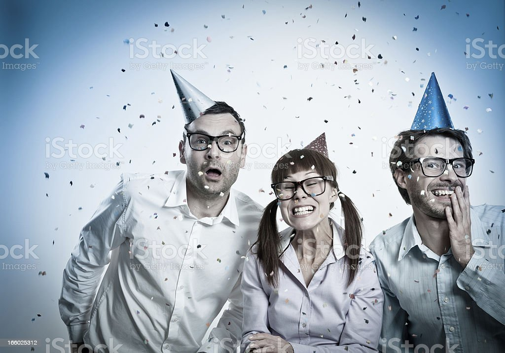 Three crazy Geek people with party hats and confetti, celebrating royalty-free stock photo