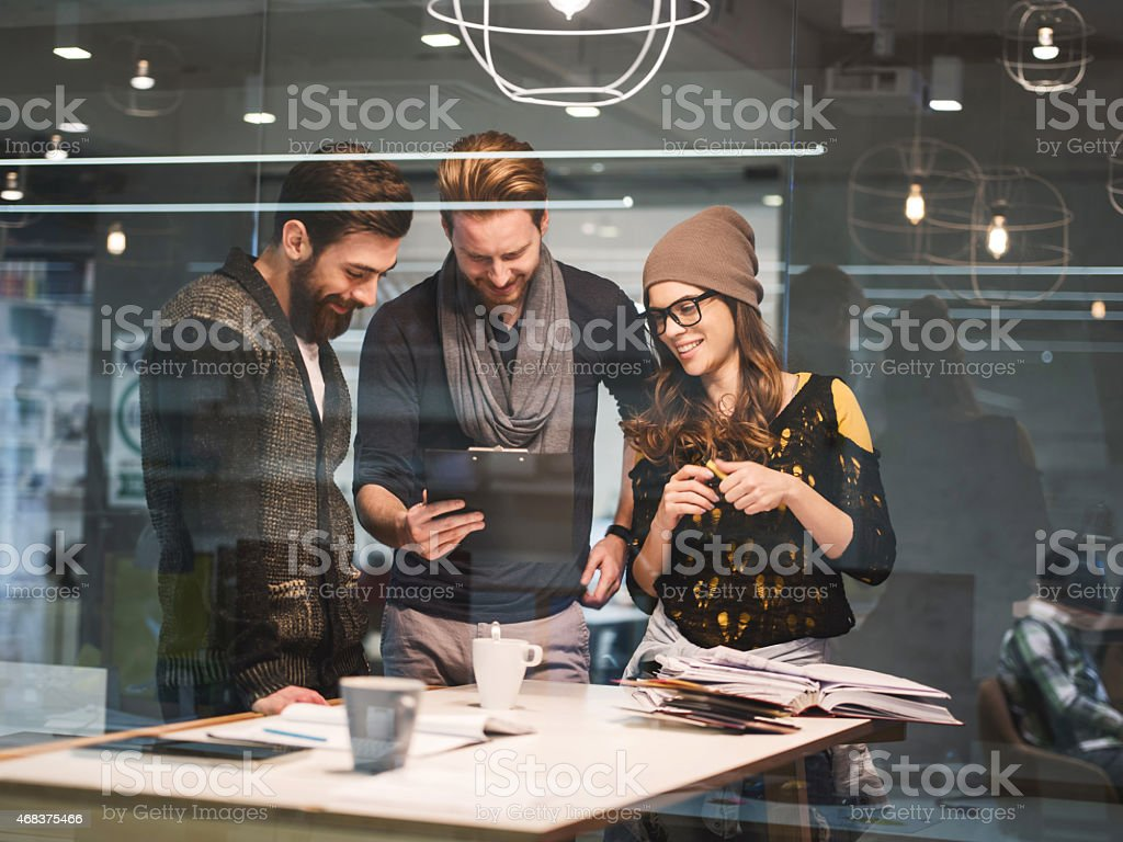 Three creative people working together on paperwork in the office. stock photo