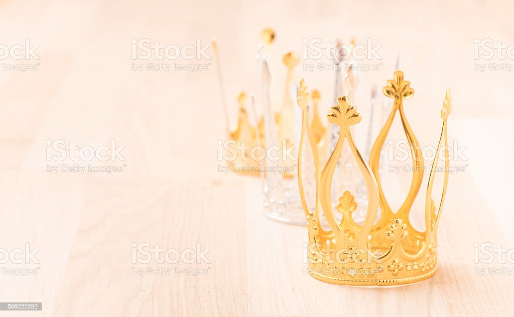 Three crowns with wood background stock photo