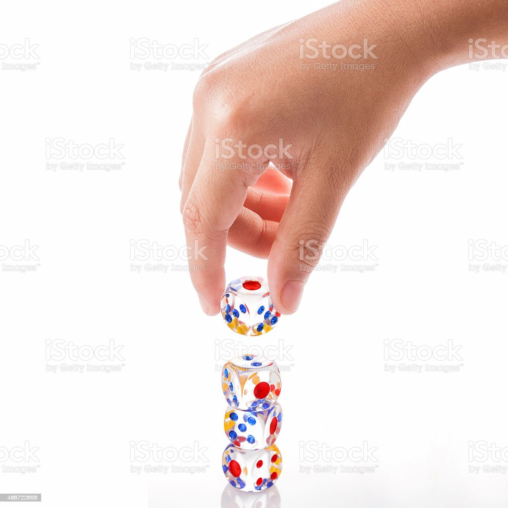 Three crystal dices stack and one crystal dice on kid hand stock photo