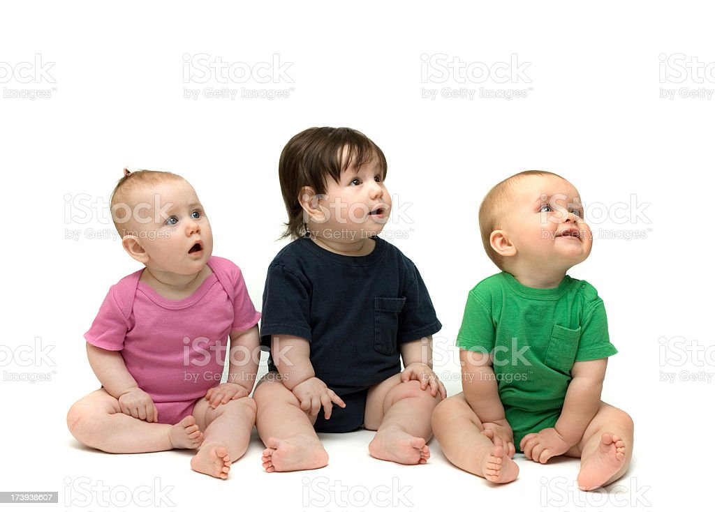 Three cute babies sitting isolated on white stock photo