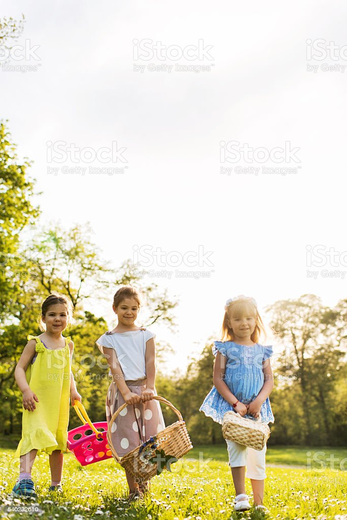Three cute girls with baskets walking in the park. stock photo