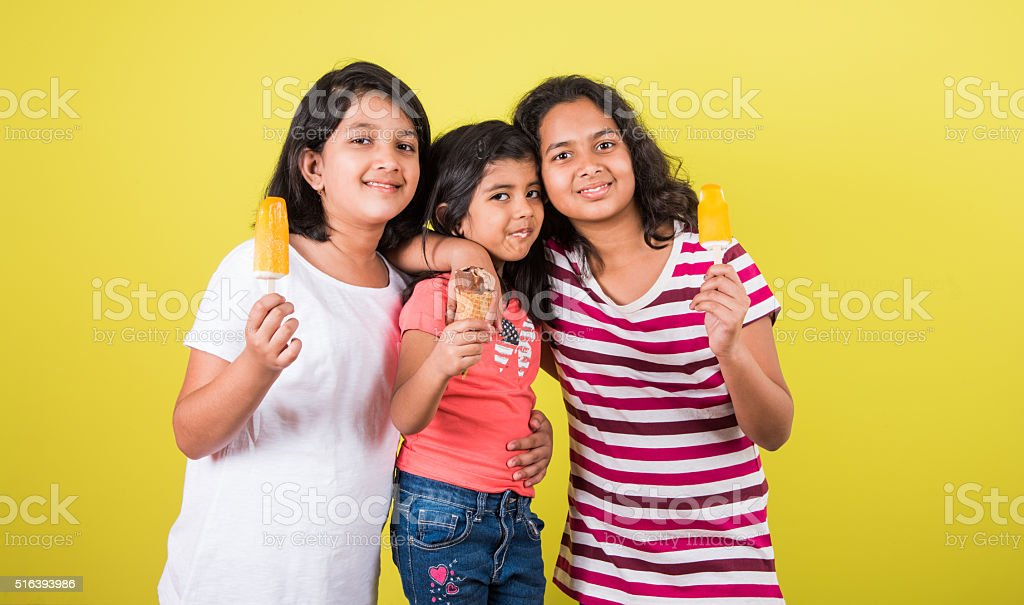 three cute little indian kids eating ice cream stock photo