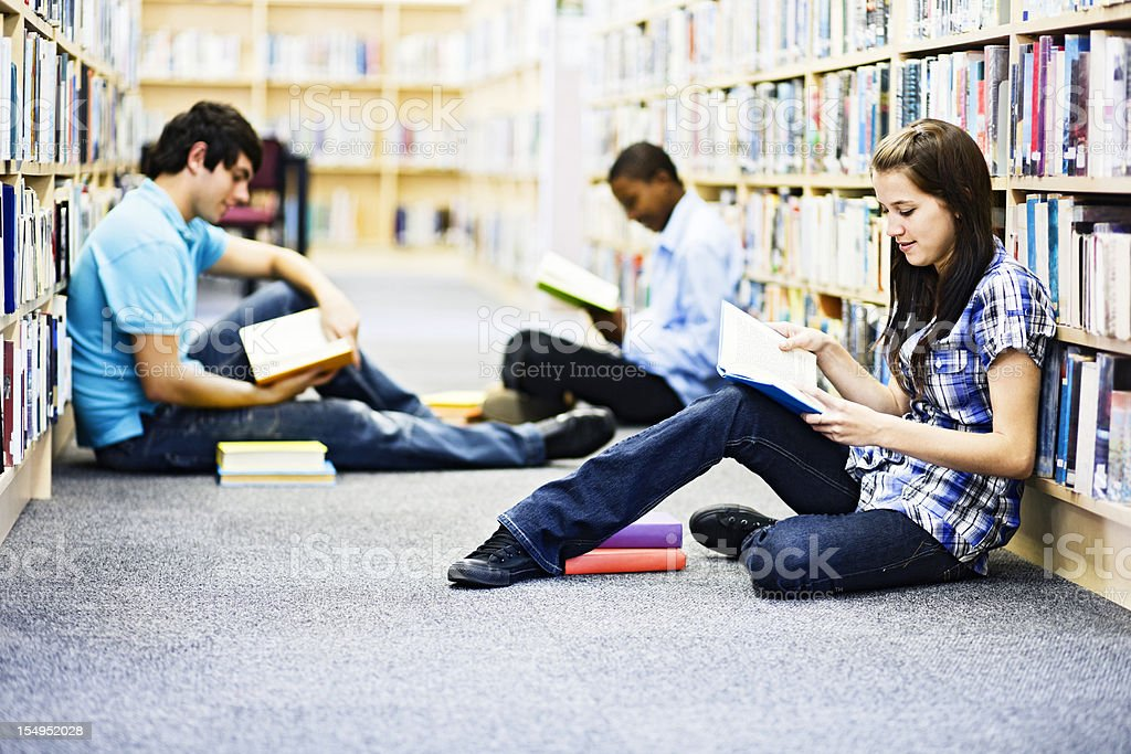 Three cute students sitting on library floor studying together royalty-free stock photo