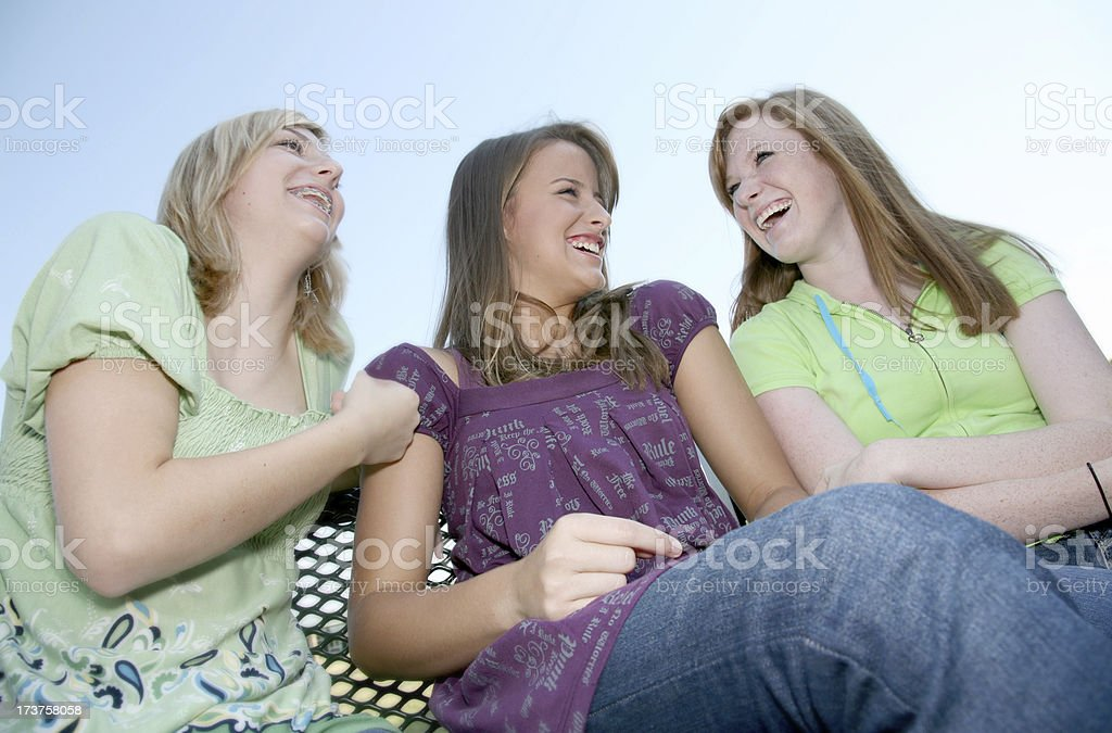 Three Cute Teenage Girls Laughing Together While Sitting Outside royalty-free stock photo