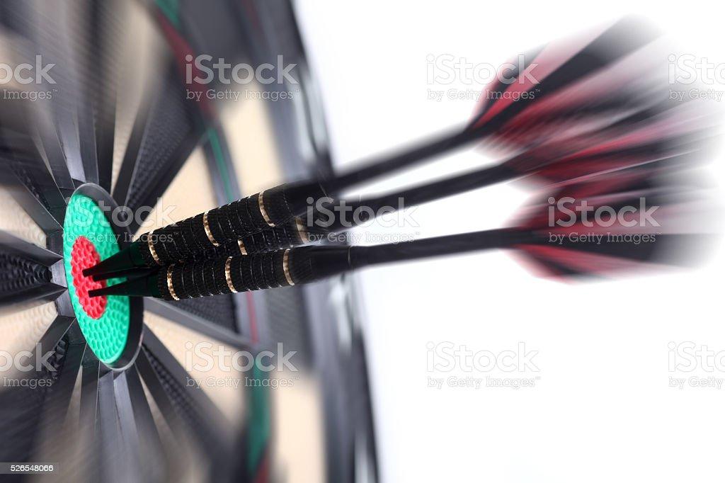 Three darts in bullseye, actionshot stock photo