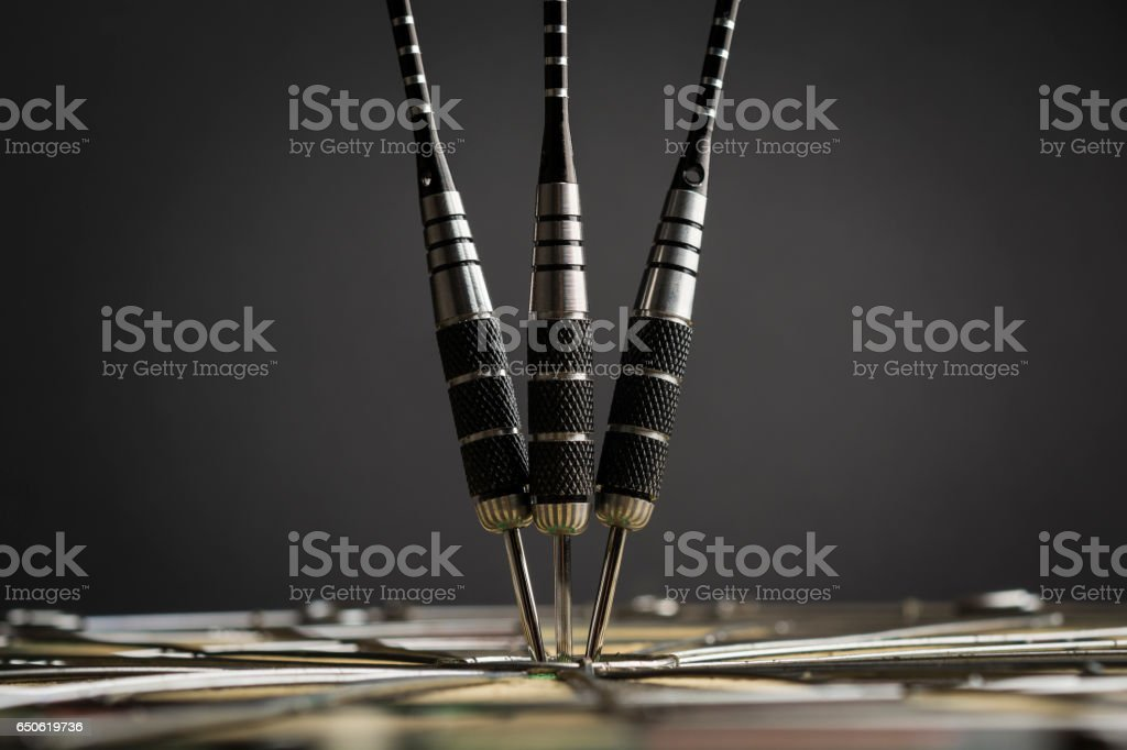 Three darts in the center of the target stock photo