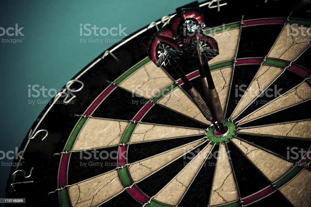 Three darts on a bullseye, close up royalty-free stock photo