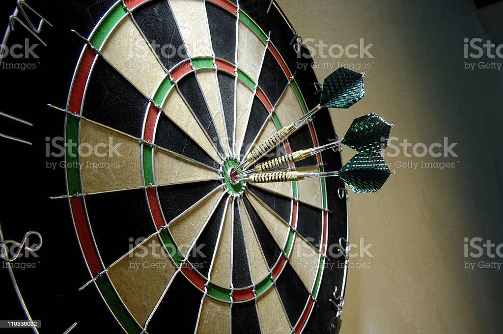 Three darts on a bullseye stock photo