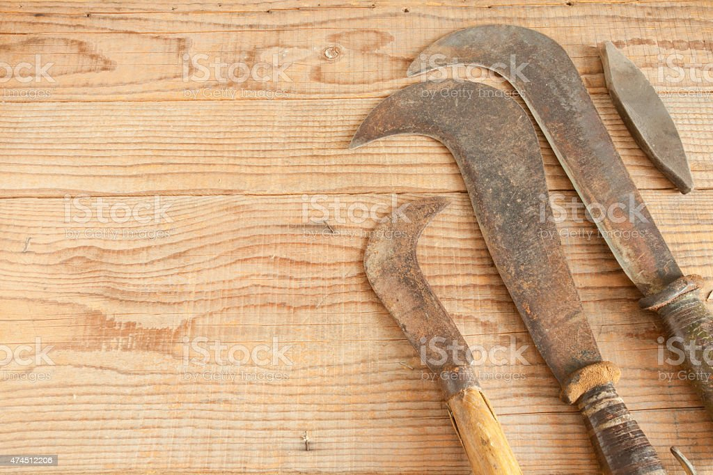 Three dated and used billhooks on wooden background stock photo