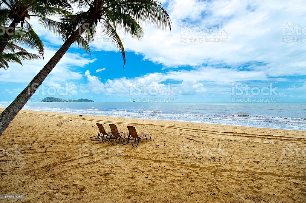 Three deck chairs on a beach stock photo