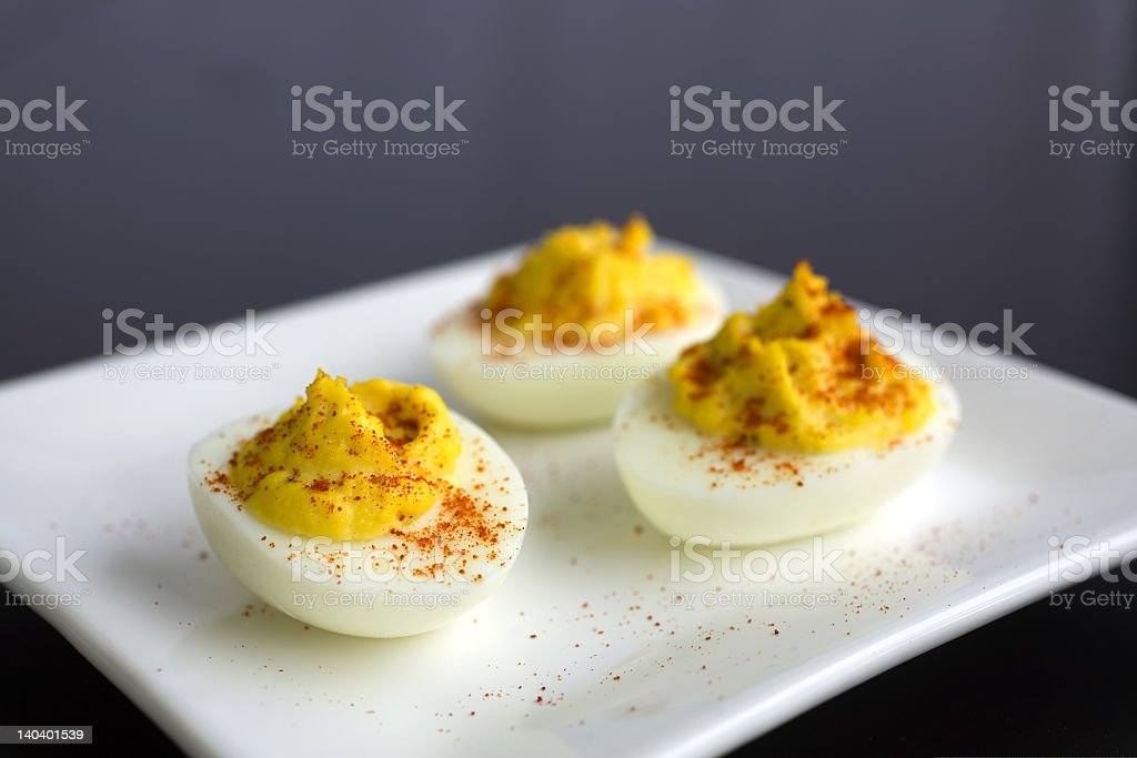 Three deviled eggs with sprinklings of smoked paprika royalty-free stock photo