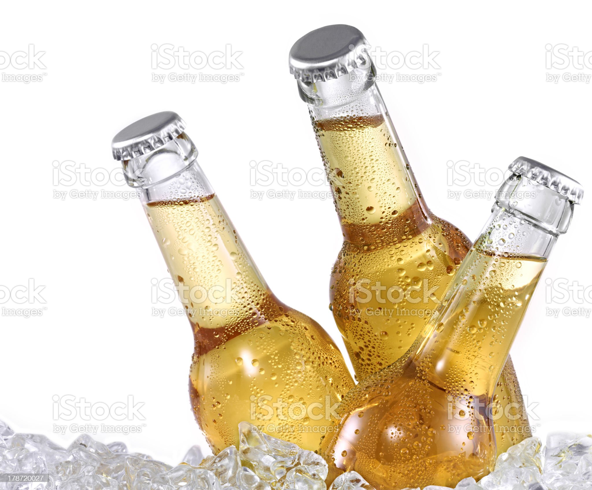 Three dewy beer bottles on ice royalty-free stock photo