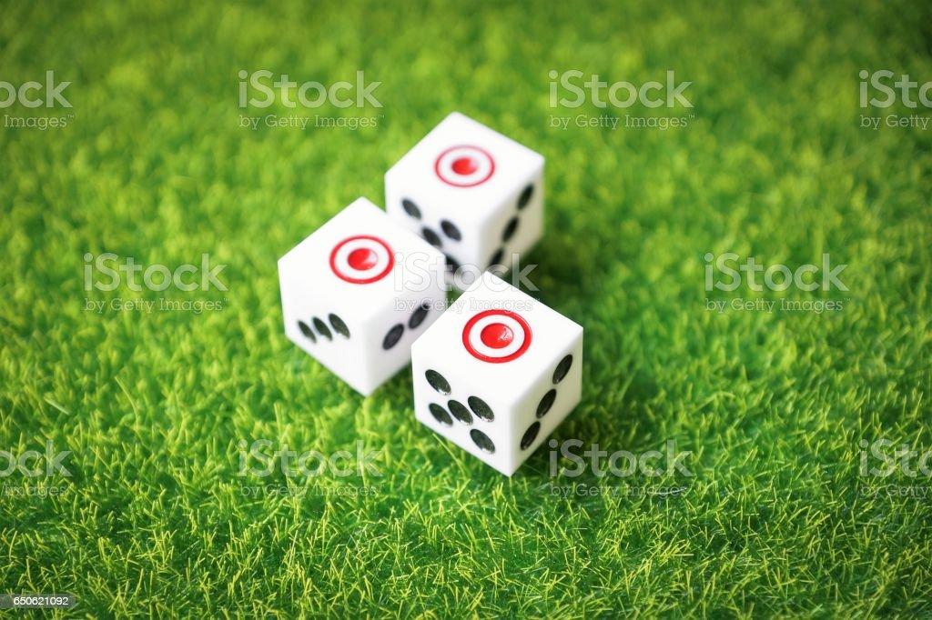 three dice cubes on green turf stock photo