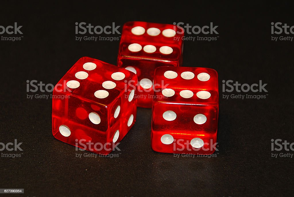 three dice on a black desk, result eighteen (18) stock photo