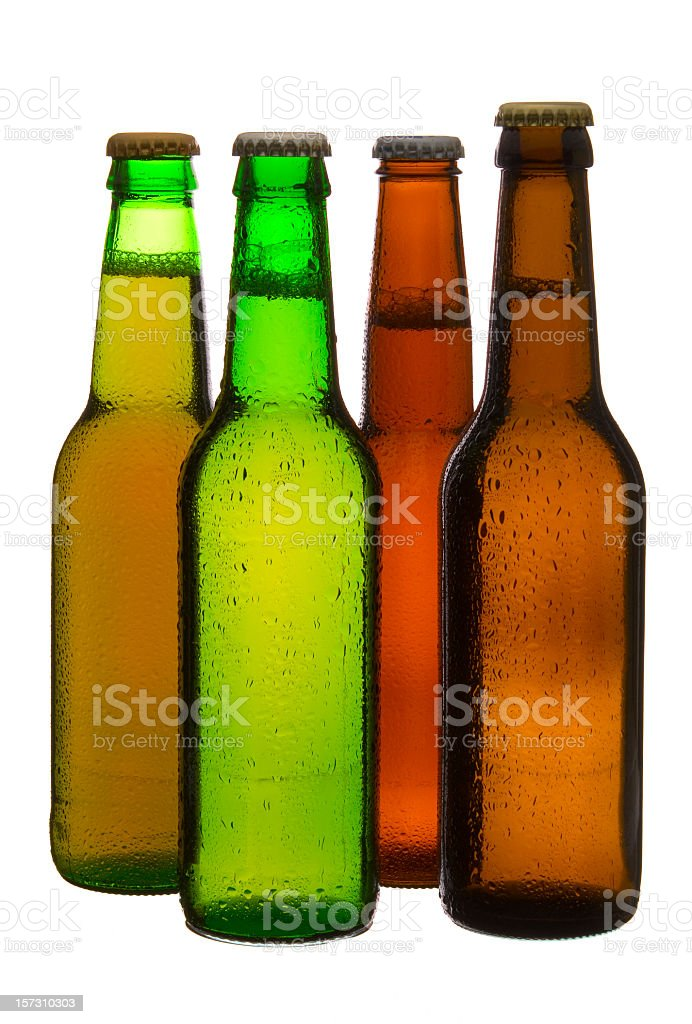 Three different colored beer bottles and caps royalty-free stock photo