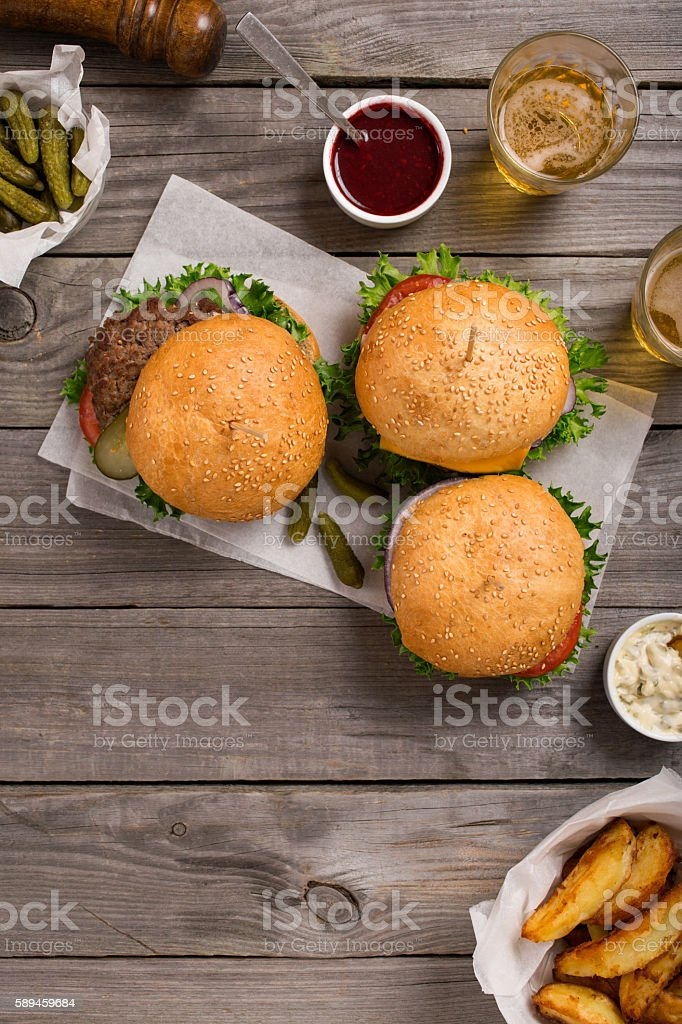 Three different hamburger on wooden table stock photo
