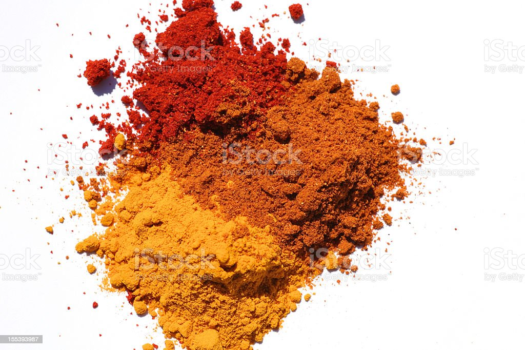 Three different powdered spices in a white background stock photo
