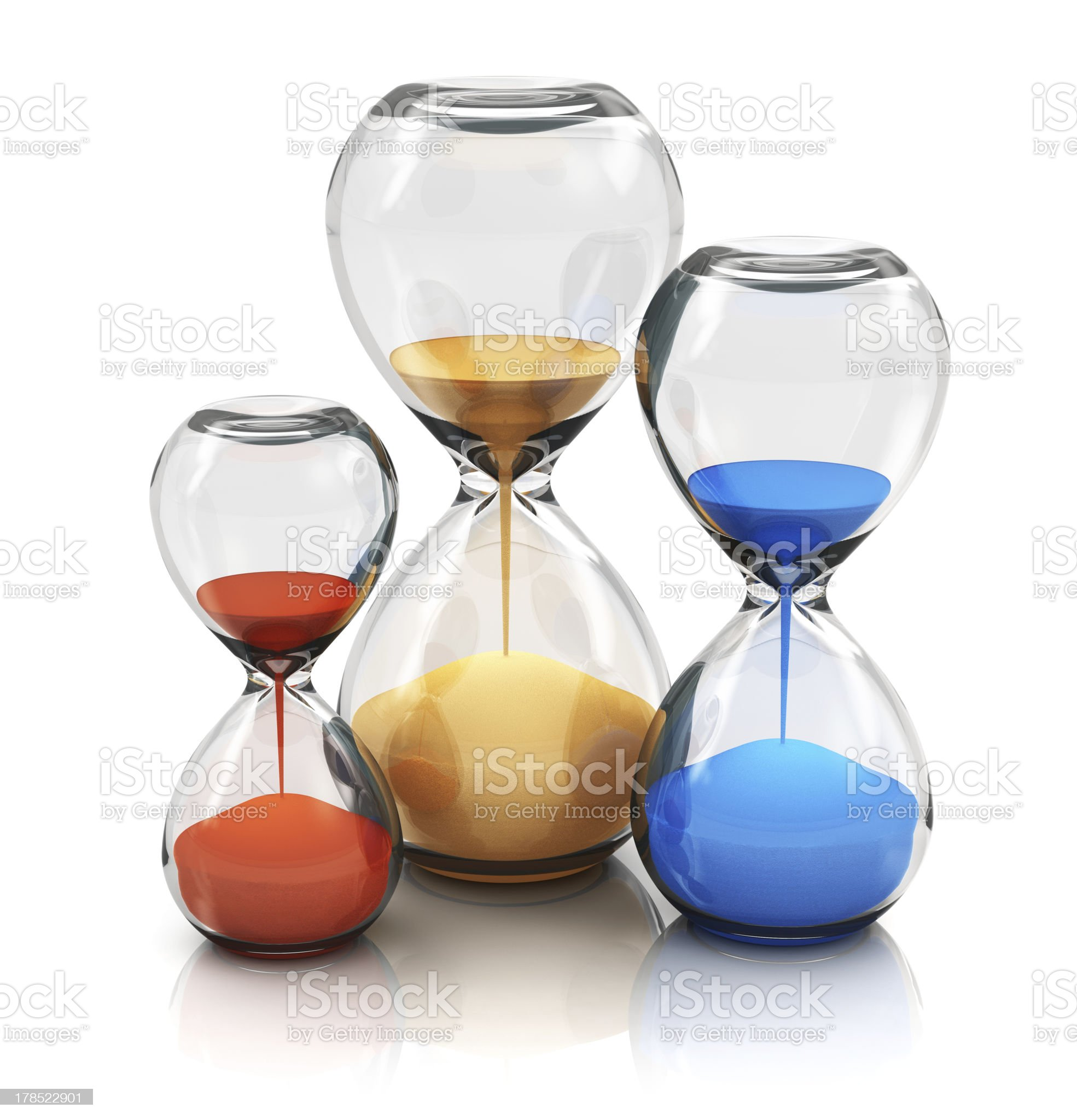 Three different size hourglasses with gold blue and red sand royalty-free stock photo
