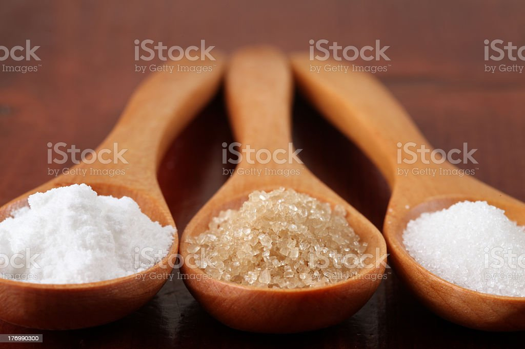 Three different types of sugar in three wooden spoons royalty-free stock photo