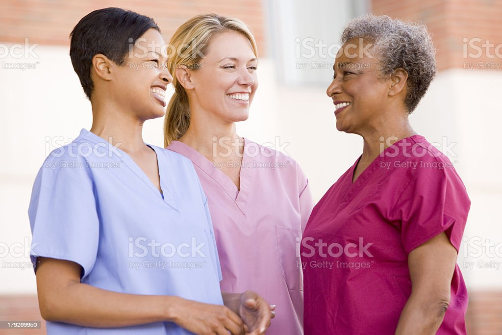 Three diverse nurses in scrubs smiling stock photo