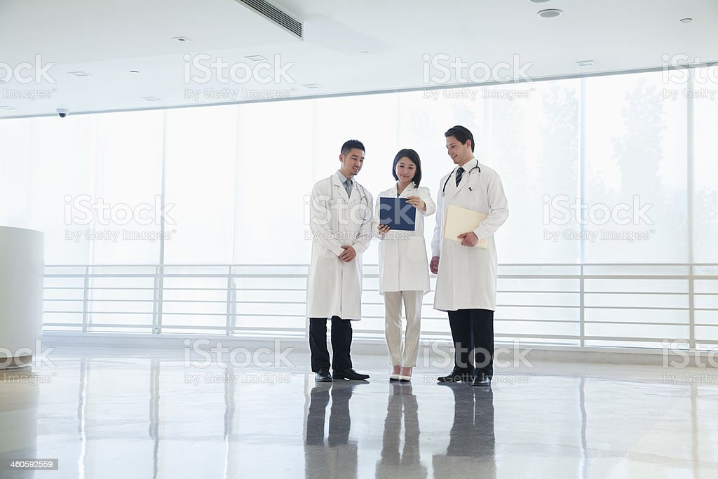 Three doctors looking down in the hospital, full length stock photo