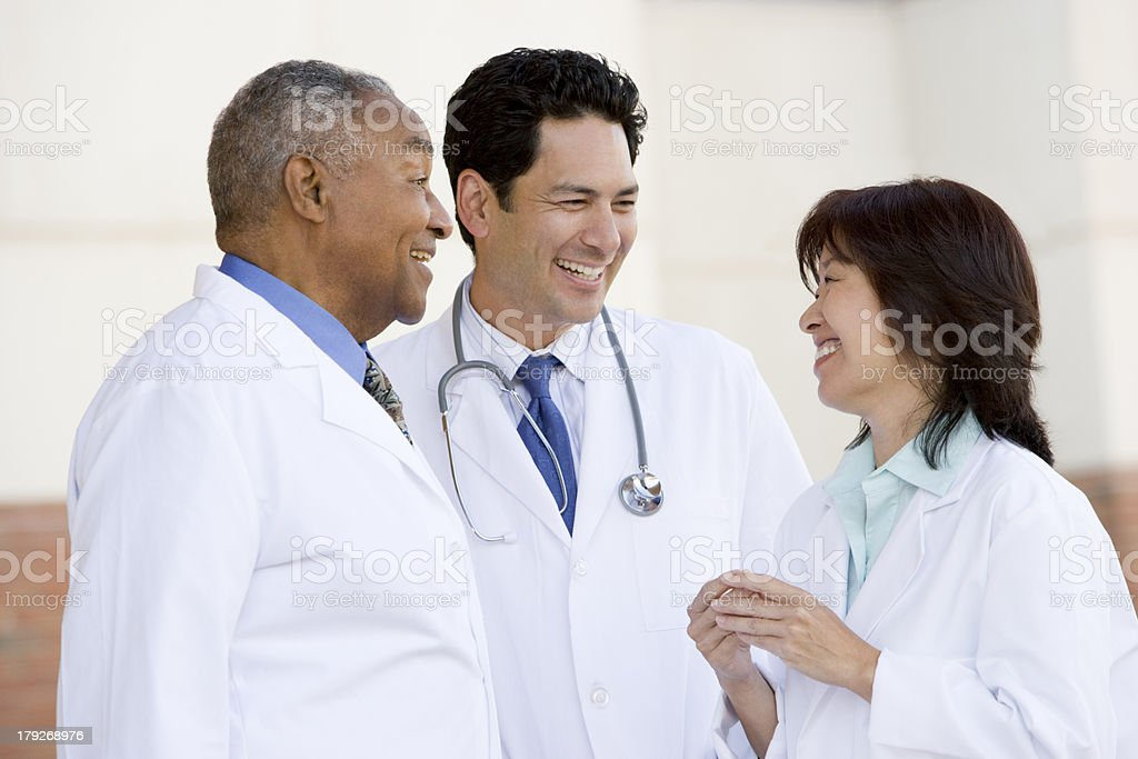 Three Doctors Standing Outside A Hospital royalty-free stock photo