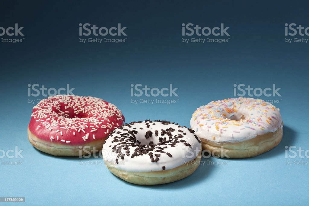 three donuts with color icing isolated on blue background royalty-free stock photo