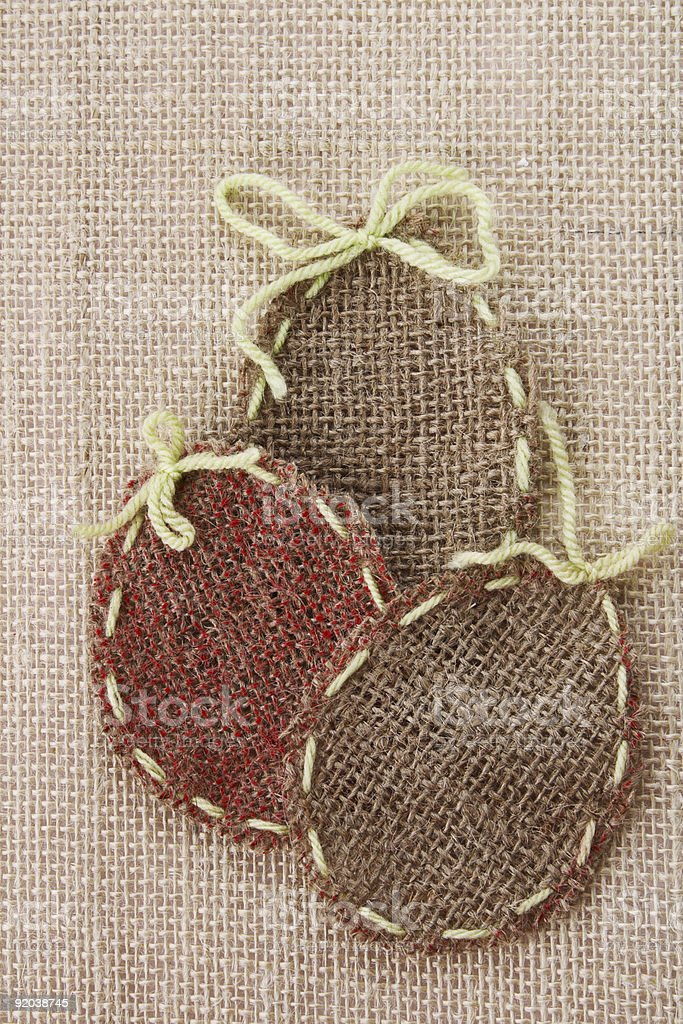 three Easter Egg shaped stitched canvas on rustic background stock photo