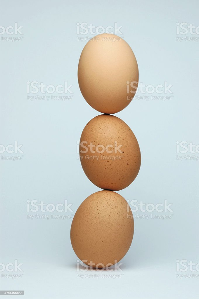 Three eggs balancing on top of each other stock photo