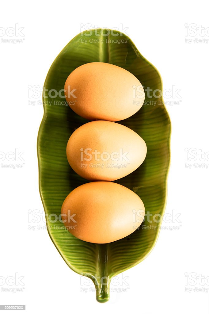 three eggs on green plate isolated on white background royalty-free stock photo