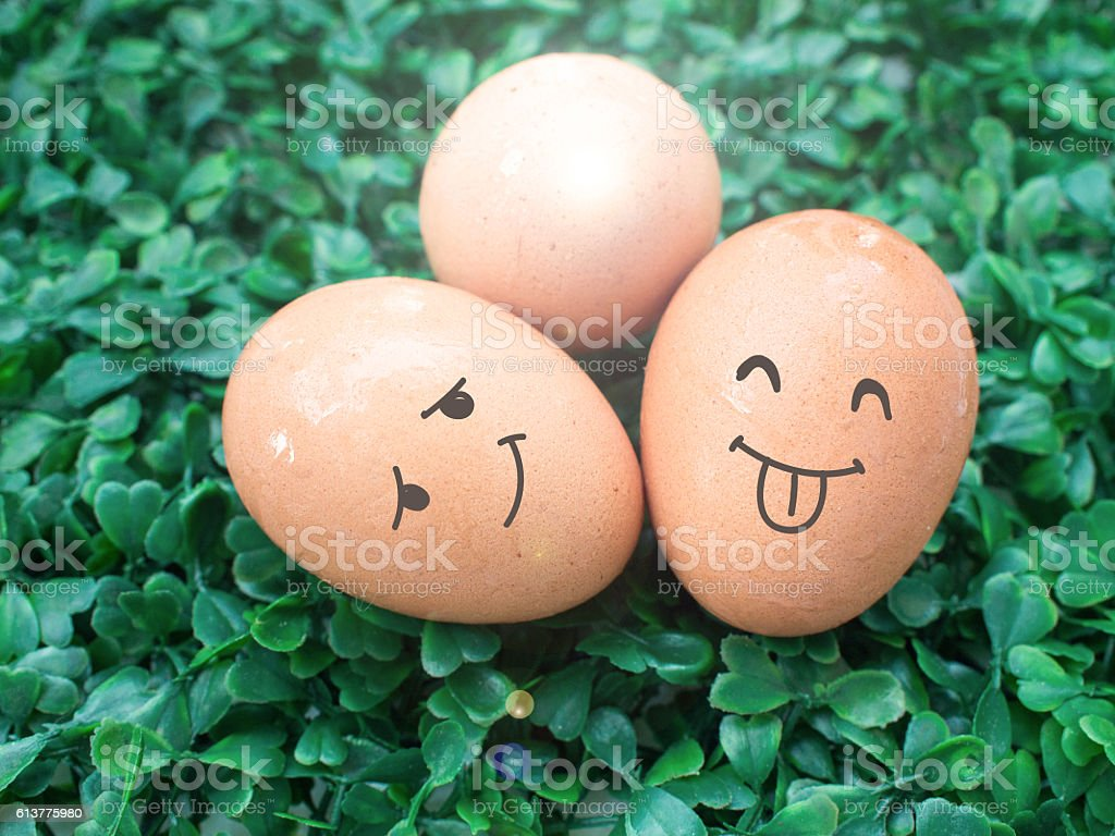 Three eggs with smile drawing put on the green grass. stock photo