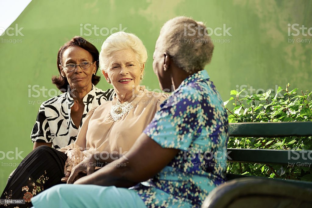 Three elderly ladies sitting on a bench and talking together royalty-free stock photo