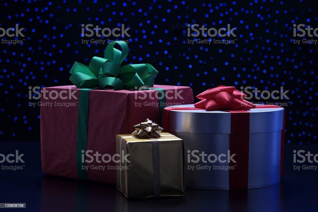 Three elegant gift boxes with ribbon against blue illumination background royalty-free stock photo