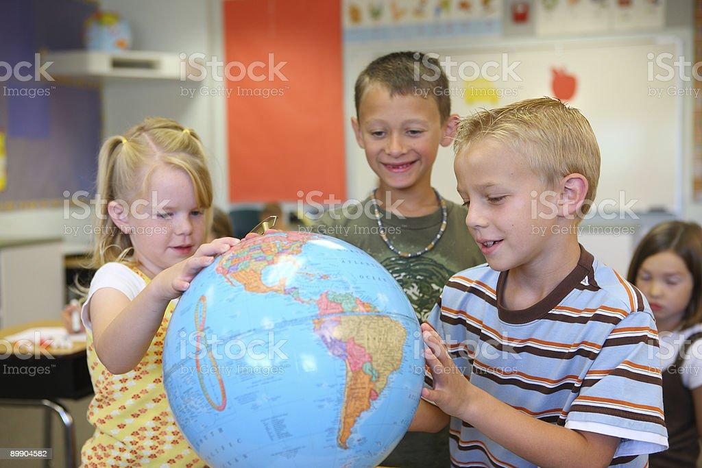 Three elementary school students look at globe royalty-free stock photo