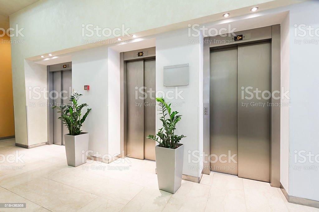 Three elevators in hotel lobby stock photo