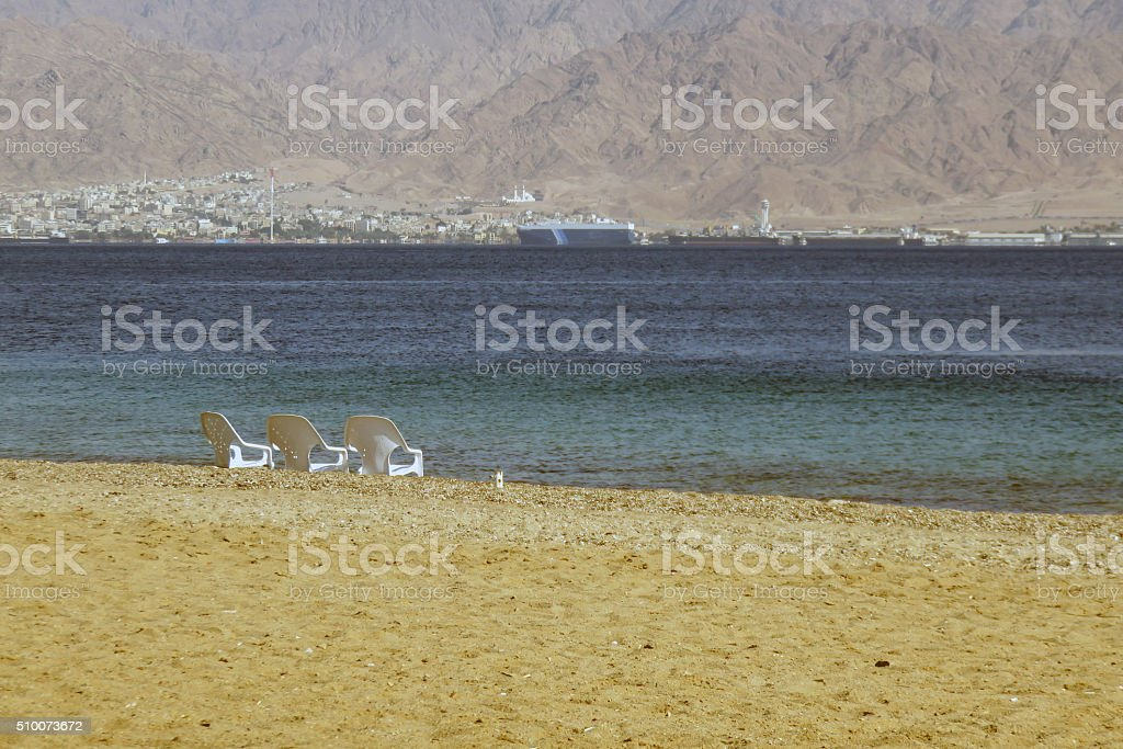 Three empty chairs on the beach of Eilat - Israel stock photo