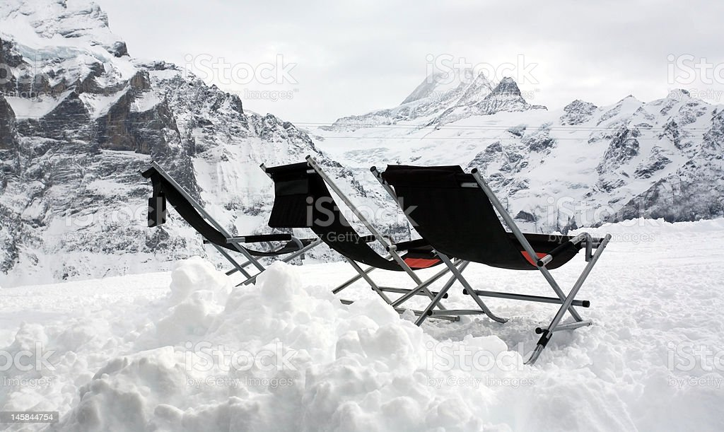 Three empty deckchairs on top of the mountains. royalty-free stock photo