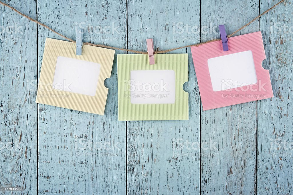 Three empty photo frames hanging with clothespins royalty-free stock photo