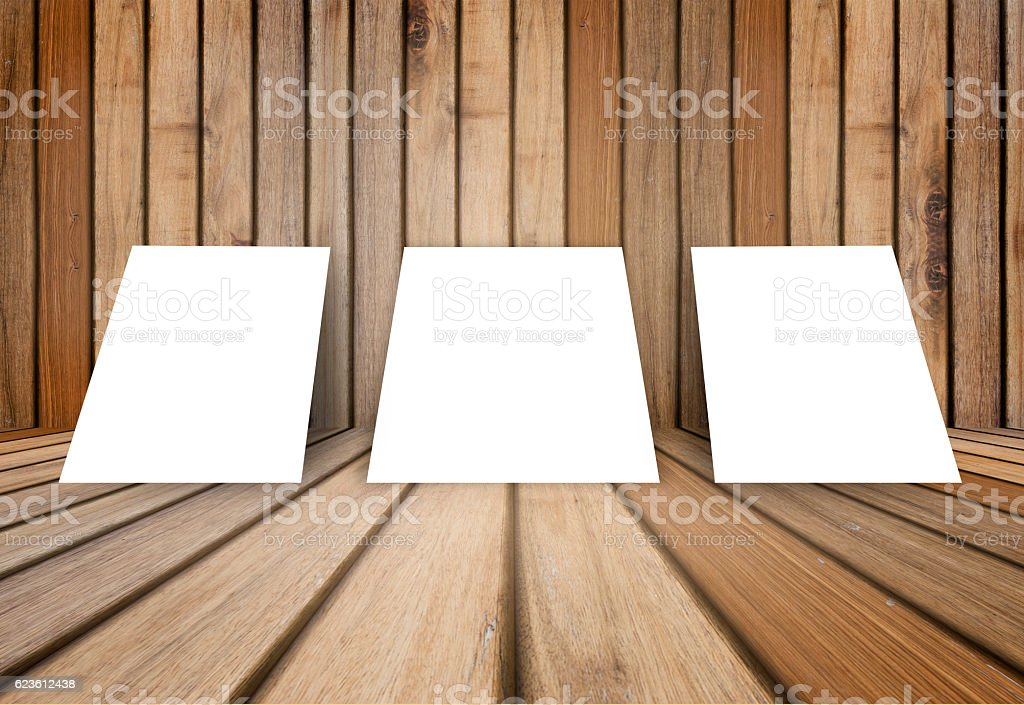 three empty poster frame against wooden interior room stock photo