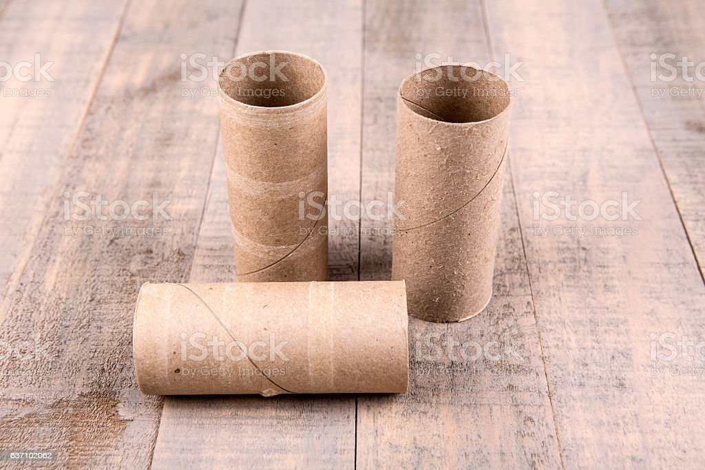 Three empty toilet paper rolls isolated on a wood background stock photo