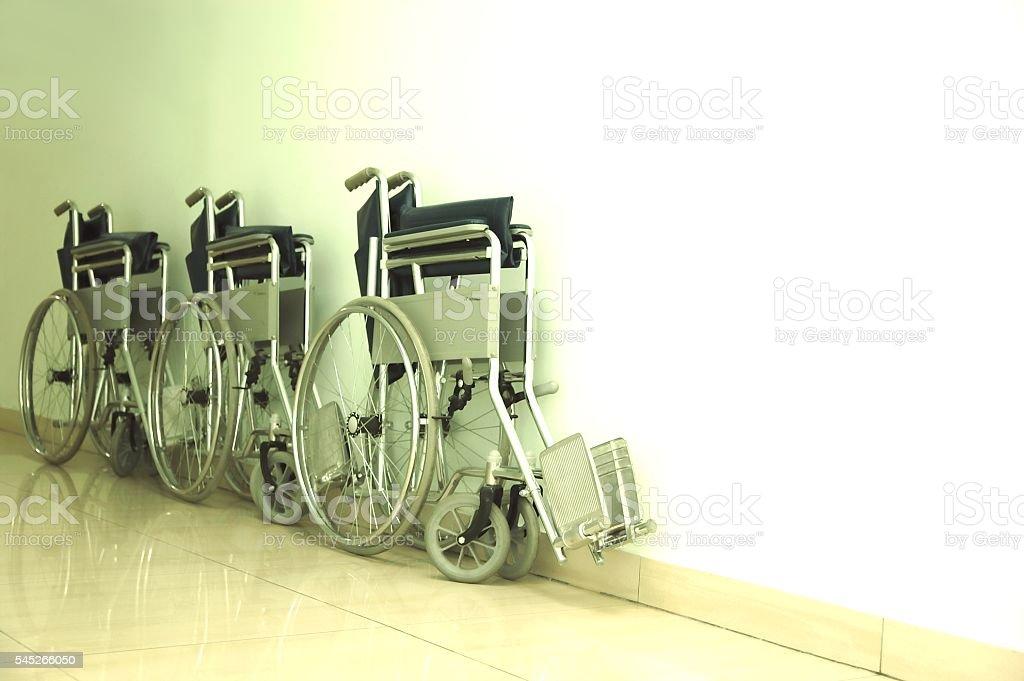 Three empty wheelchairs parked at a hospital corridor foto de stock libre de derechos