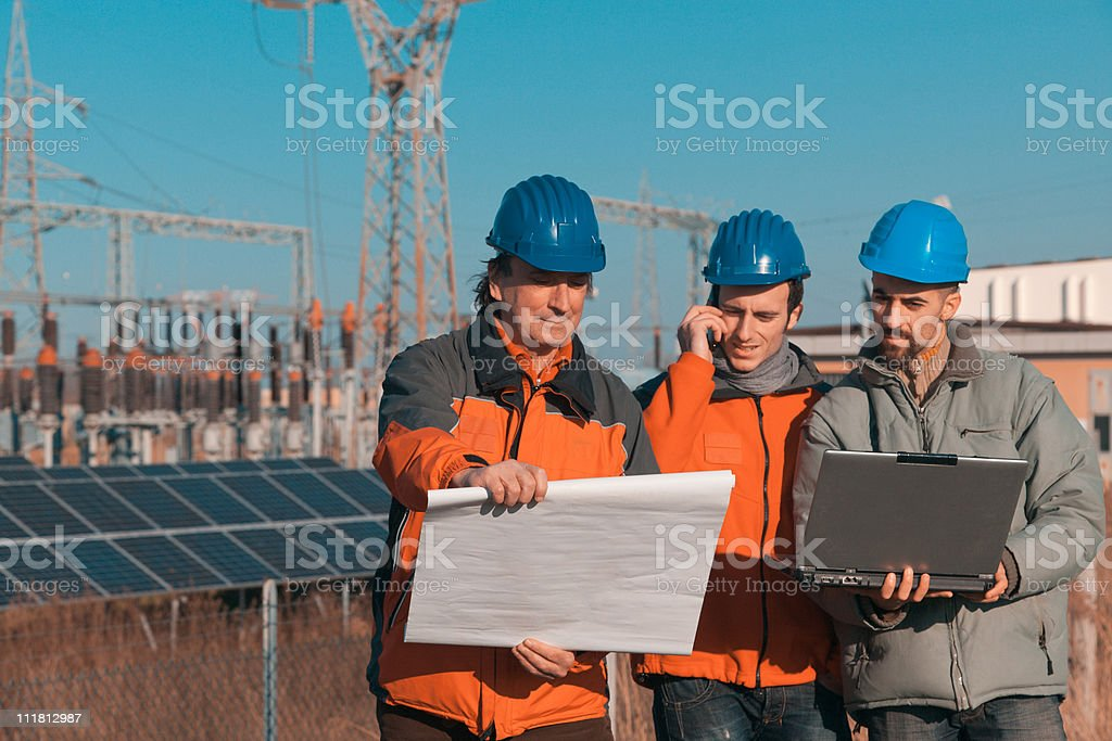 Three Engineers at Work In a Solar Power Station royalty-free stock photo