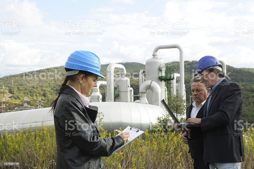 Three Engineers in a Geothermal Power Station stock photo