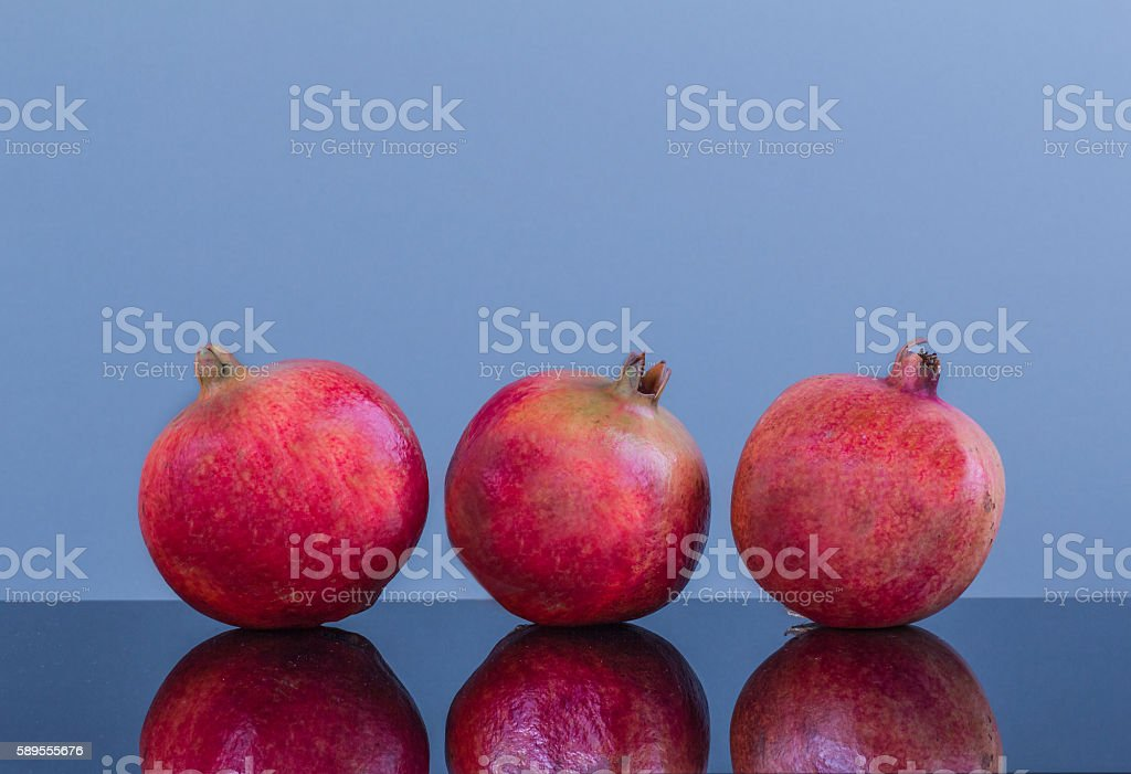 Three equally large in size pomegranate on a blue background stock photo