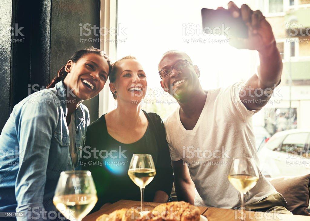 Three ethnic friends taking a selfie stock photo